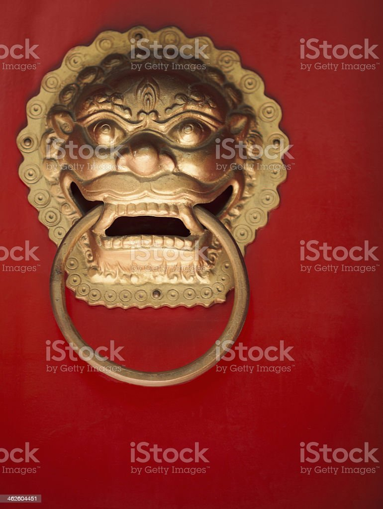 Close-up of ornate gold doorknocker on red door royalty-free stock photo