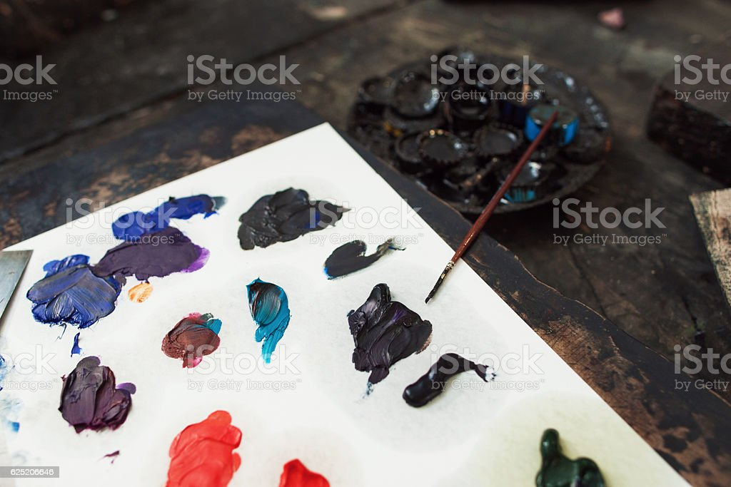 Close-up of palette with paints and paintbrush stock photo