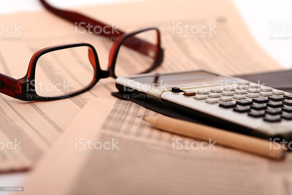 A close-up of papers, glasses and a calculator royalty-free stock photo