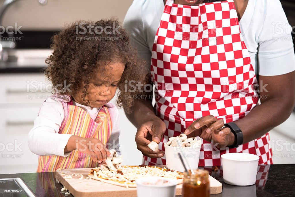 Close-up Of Parent/ Carer And Biracial Little Girl Making Pizza stock photo