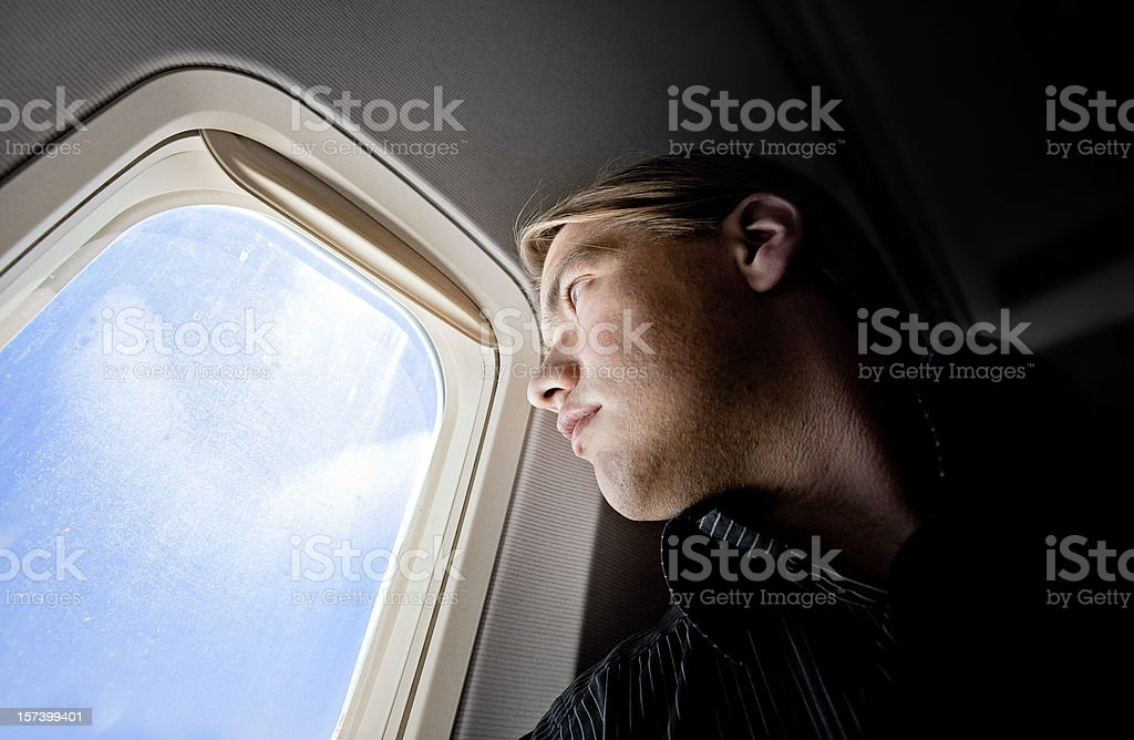 Close-up of passenger looking out through window on a plane stock photo