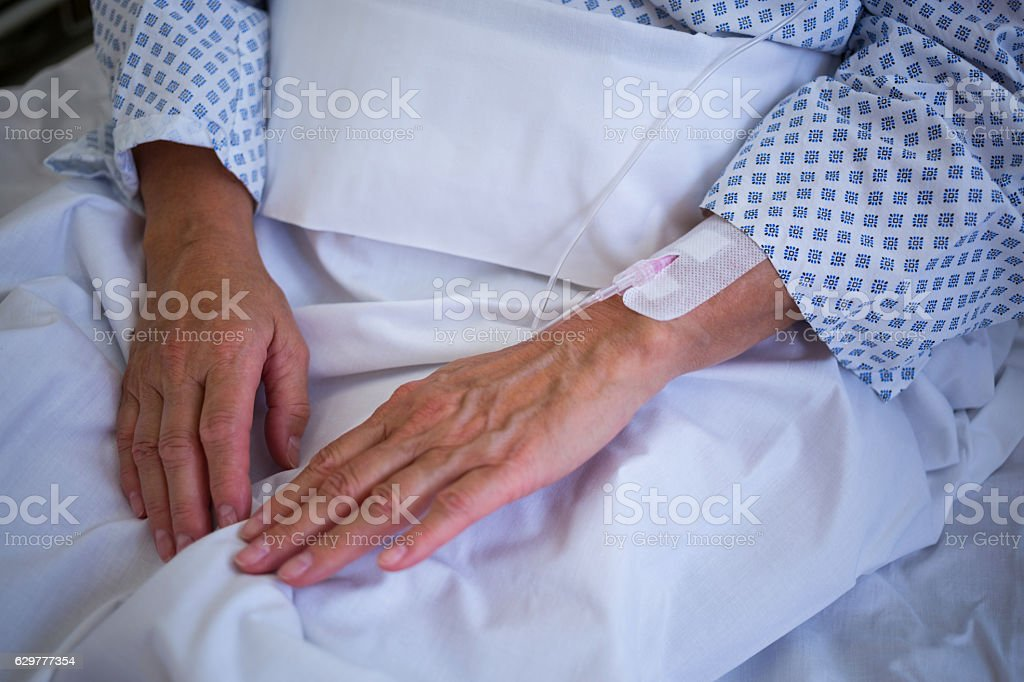 Close-up of patients hand with iv drip stock photo