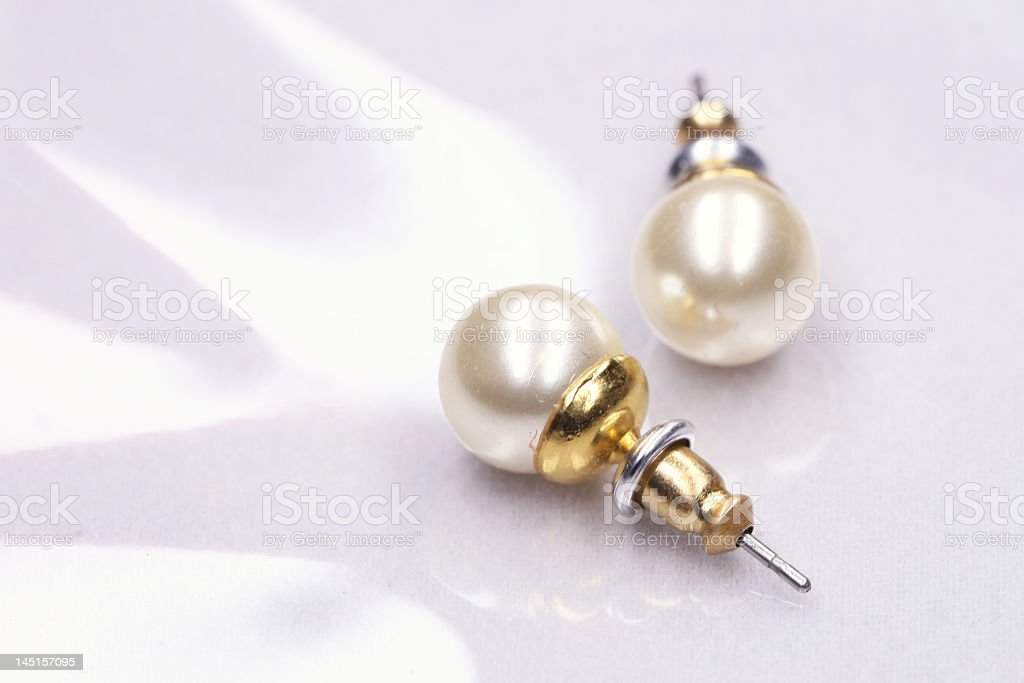 Close-up of pearl earrings on white background stock photo