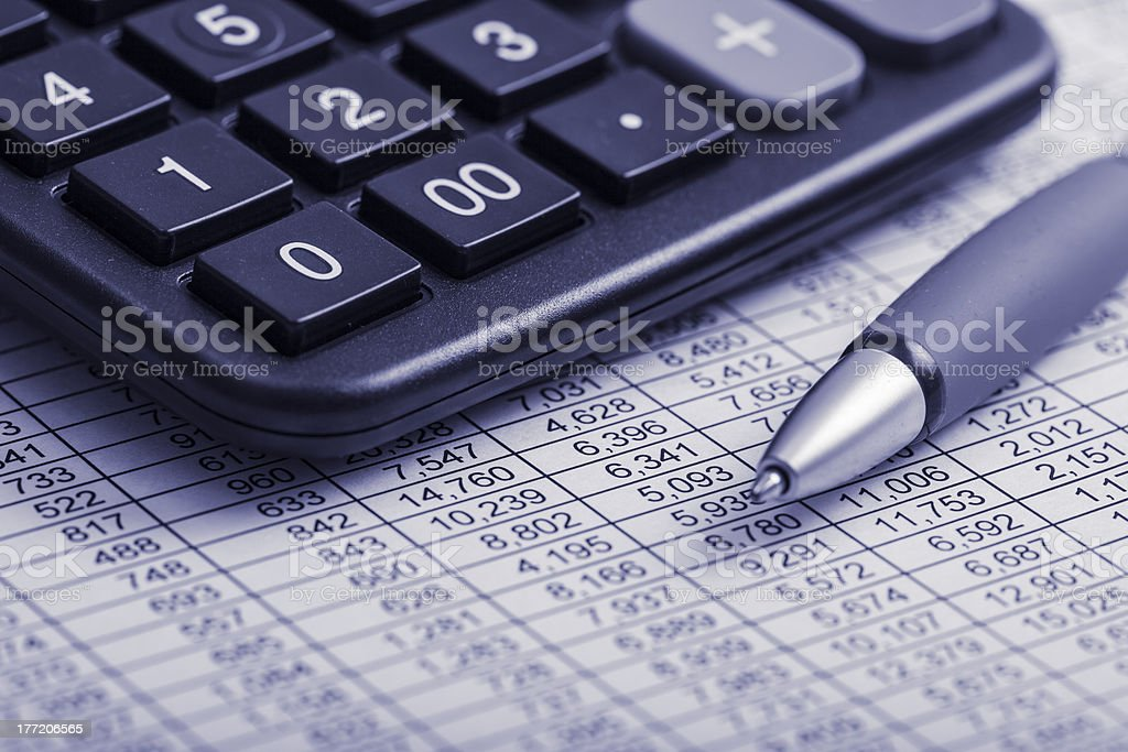 Close-up of pen and calculator on financial report royalty-free stock photo