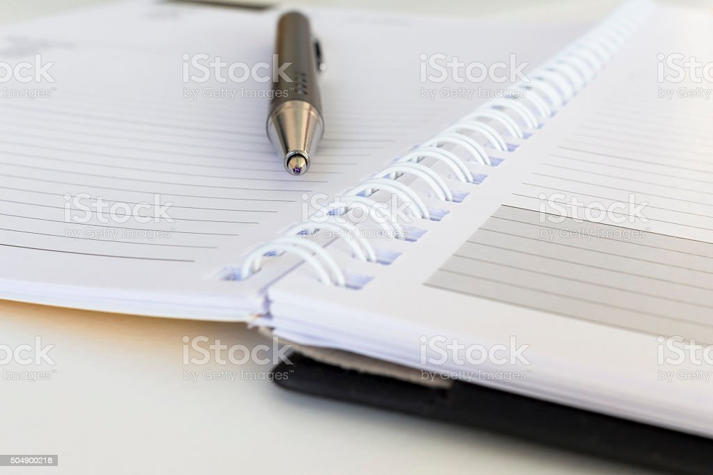 close-up of pen and diary calendar on an office desk stock photo