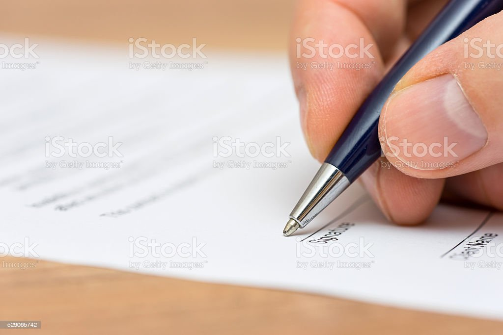 closeup of pen and human fingers  signing document stock photo