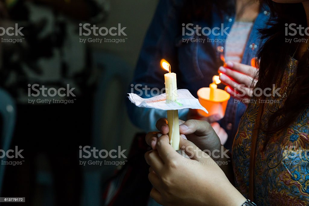 Closeup of people holding candle vigil in dark seeking hope stock photo