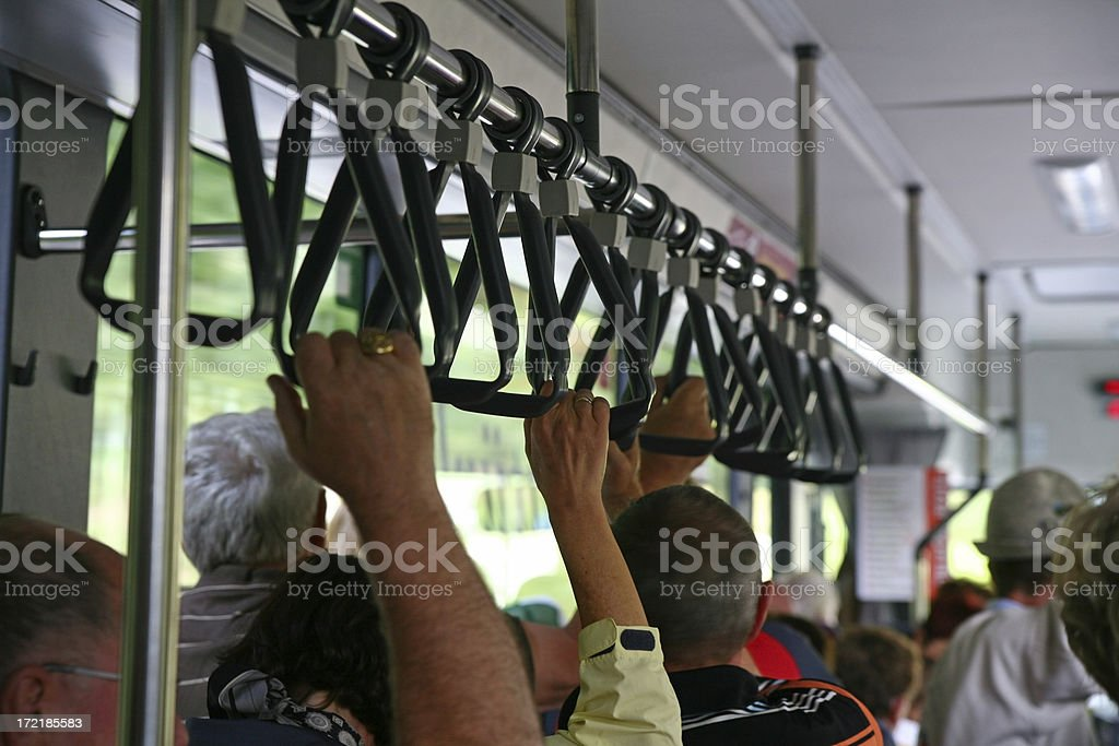 Close-up of people holding on while standing in a bus royalty-free stock photo