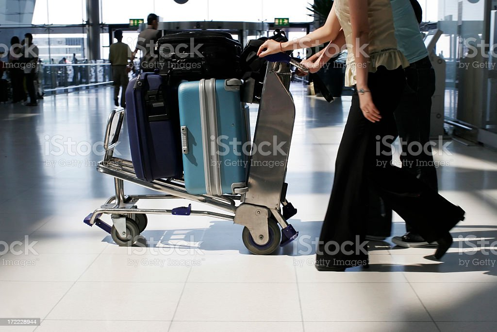 Close-up of people pushing a luggage rack at the airport stock photo