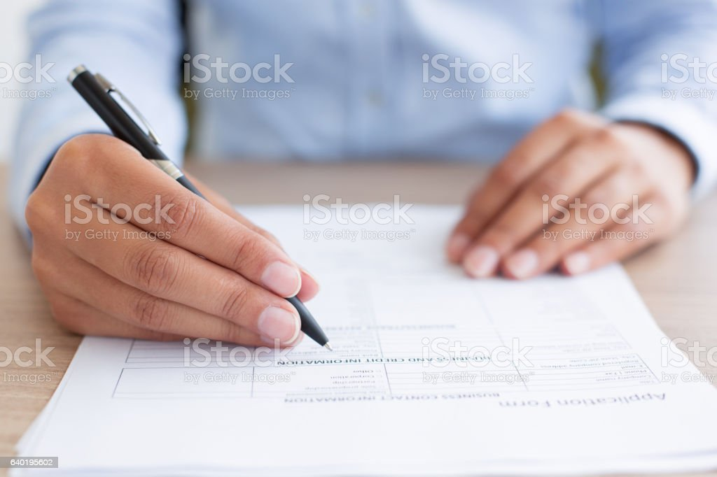 Closeup of Person Completing Application Form stock photo
