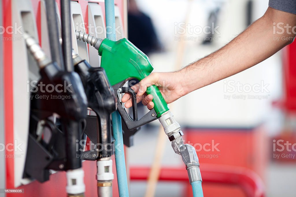 Close-up of person picking up green fuel pump stock photo
