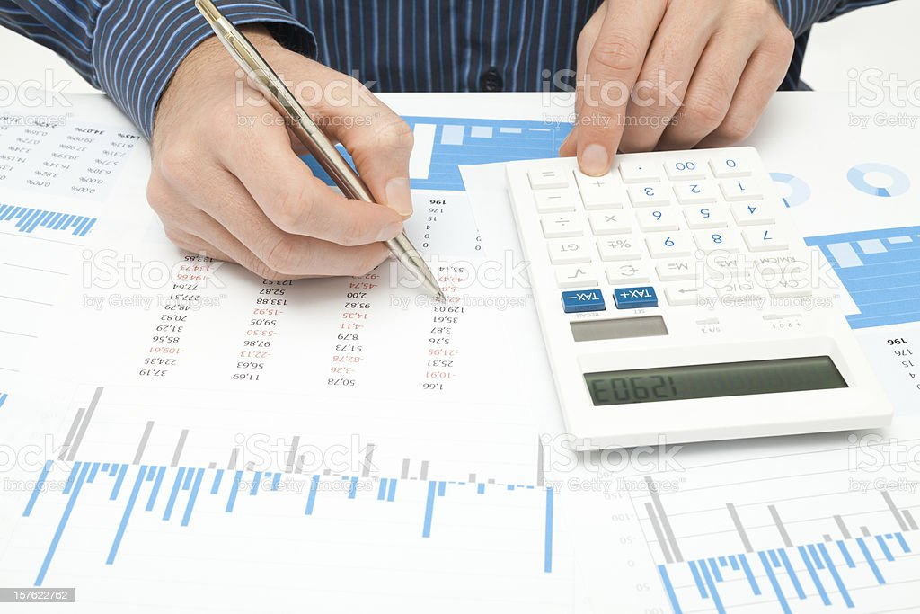 Close-up of person using calculator and paper for business stock photo