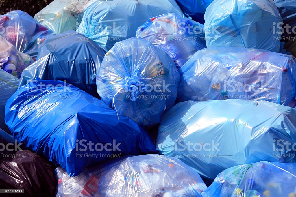 Close-up of pile of full blue trash bags stock photo