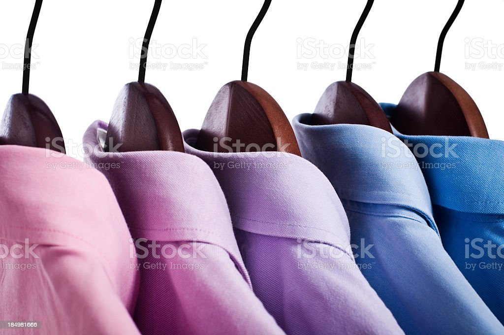 Close-up of pink, blue button down shirts hanging on hangers royalty-free stock photo