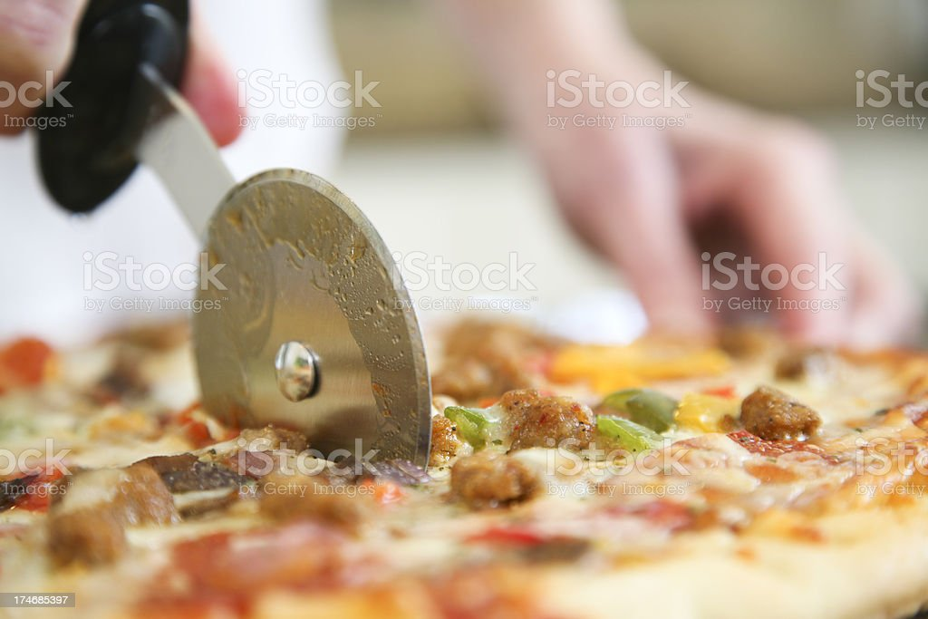 Closeup of Pizza Being Cut by Cutter stock photo