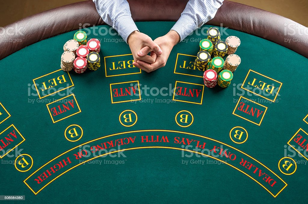 Closeup of poker player with chips at green casino table stock photo