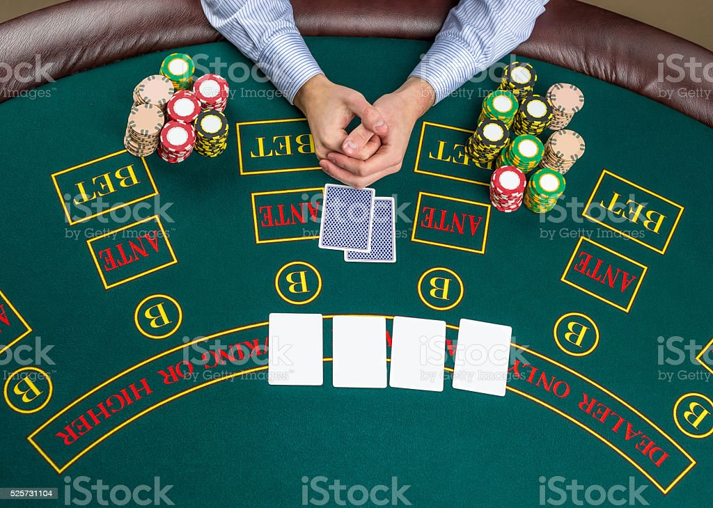 Closeup of poker player with playing cards and chips stock photo