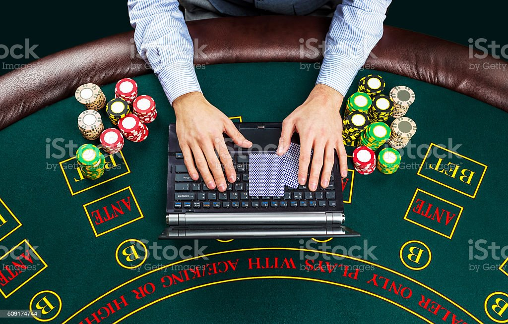 Closeup of poker player with playing cards, laptop and chips stock photo