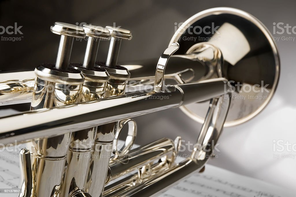 Close-up of polished trumpet sitting atop a sheet of music stock photo