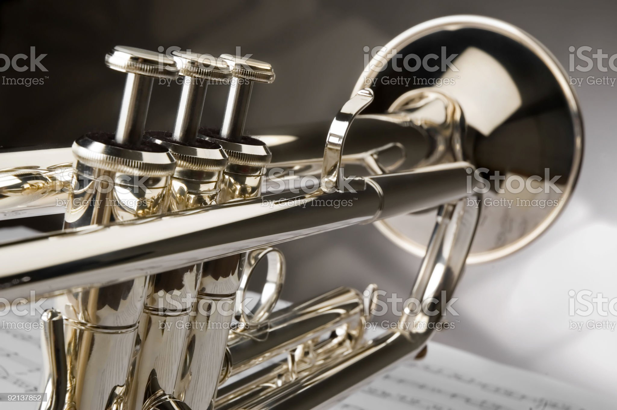 Close-up of polished trumpet sitting atop a sheet of music royalty-free stock photo