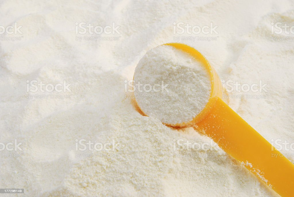 Close-up of powdered milk scooped up with a yellow spoon stock photo