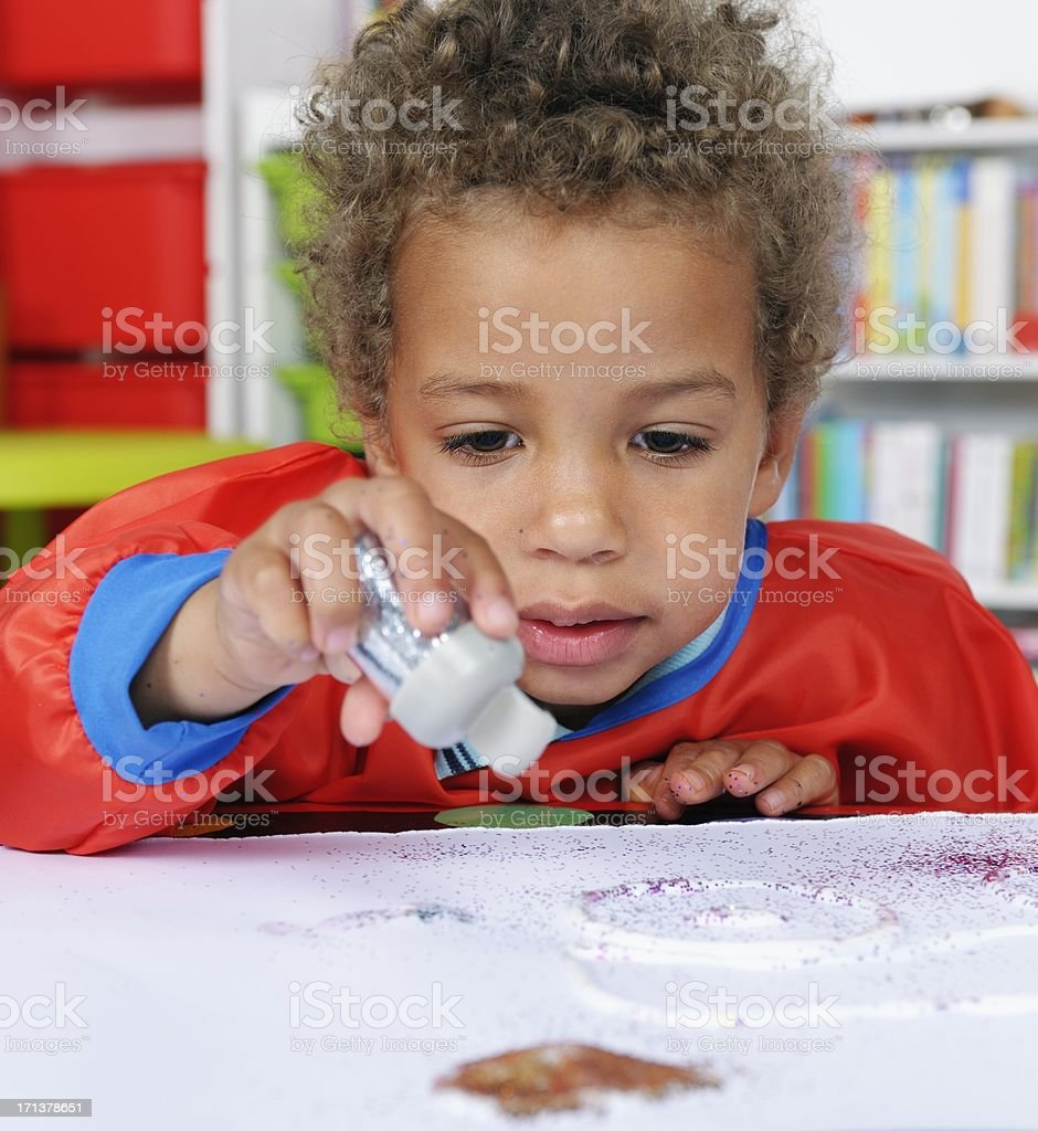 Close-up Of Preschooler Using Glue And Glitter To Create Art royalty-free stock photo