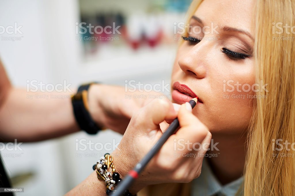 Close-up of professional make-up artist applying contour on lips stock photo