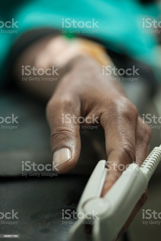 Close-up of pulse oximeter sensor on patient's left index finger. stock photo