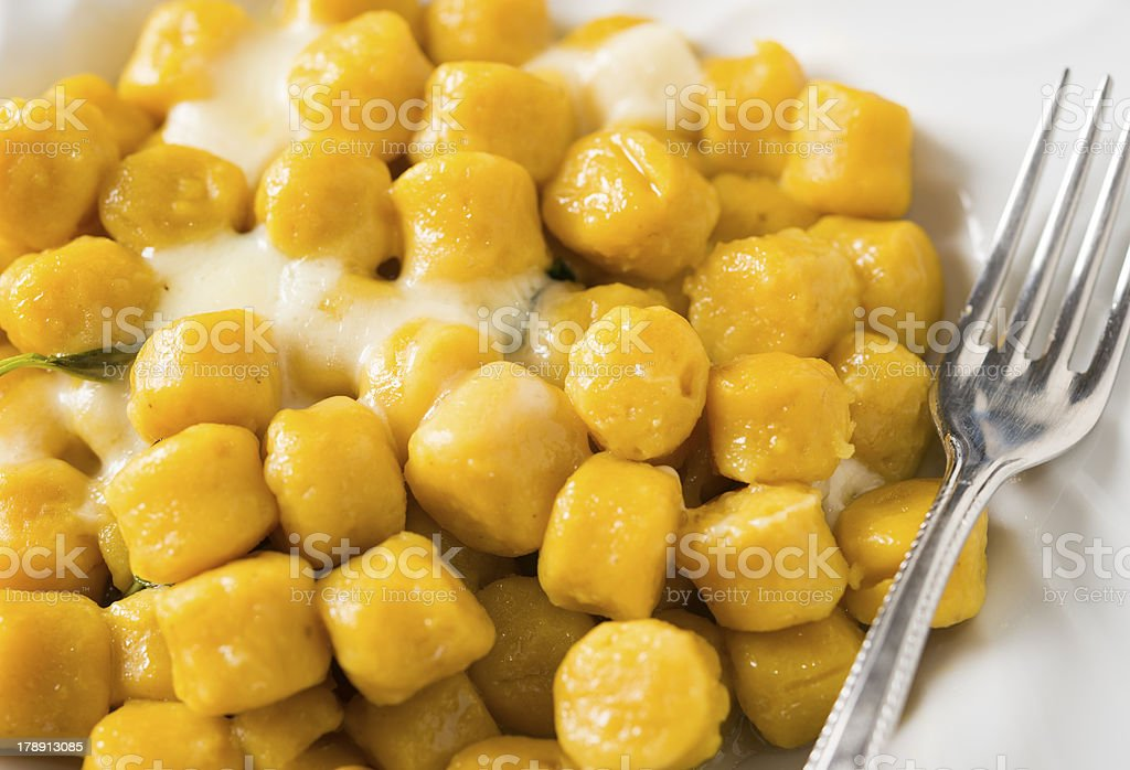 Closeup of Pumpkin Potato Gnocchi with cheese butter and basil royalty-free stock photo