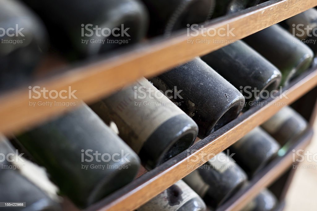 Close-up of racks of dusty vintage red wine bottles royalty-free stock photo