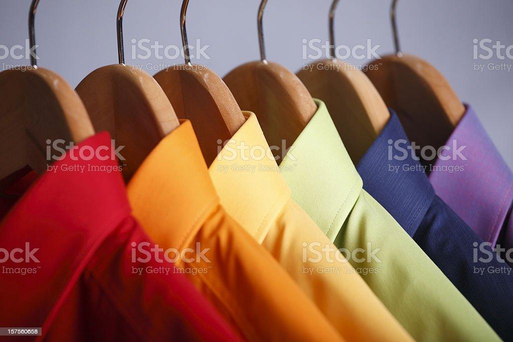Close-up of rainbow shirt collars hanging in closet stock photo