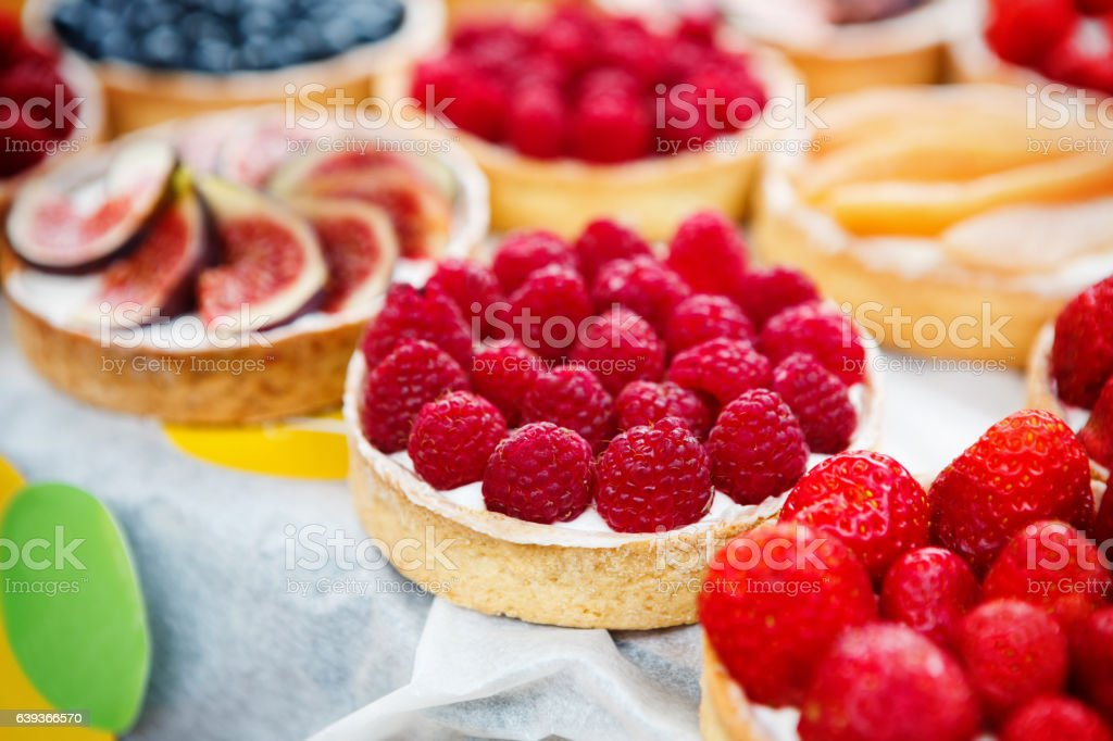 Closeup of raspberry tart dessert tray assorted stock photo