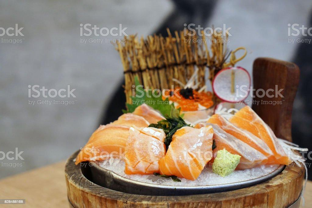 Closeup of raw fresh salmon sliced also known as sashimi on ice with wasabi. stock photo