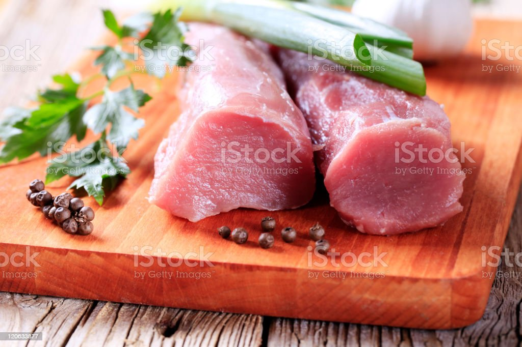Close-up of raw pork tenderloin with spices stock photo