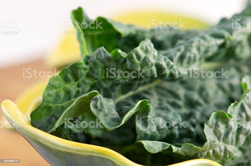 Close-up of Raw Tuscan Kale Leaves in Bowl stock photo