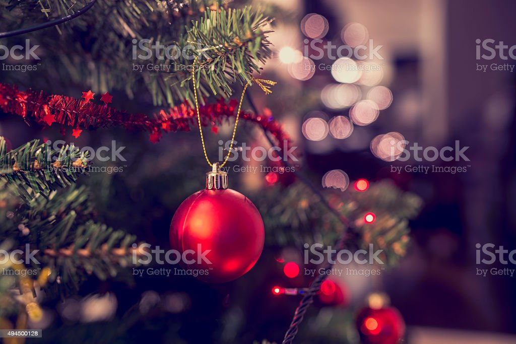 Closeup of red bauble hanging from Christmas tree stock photo