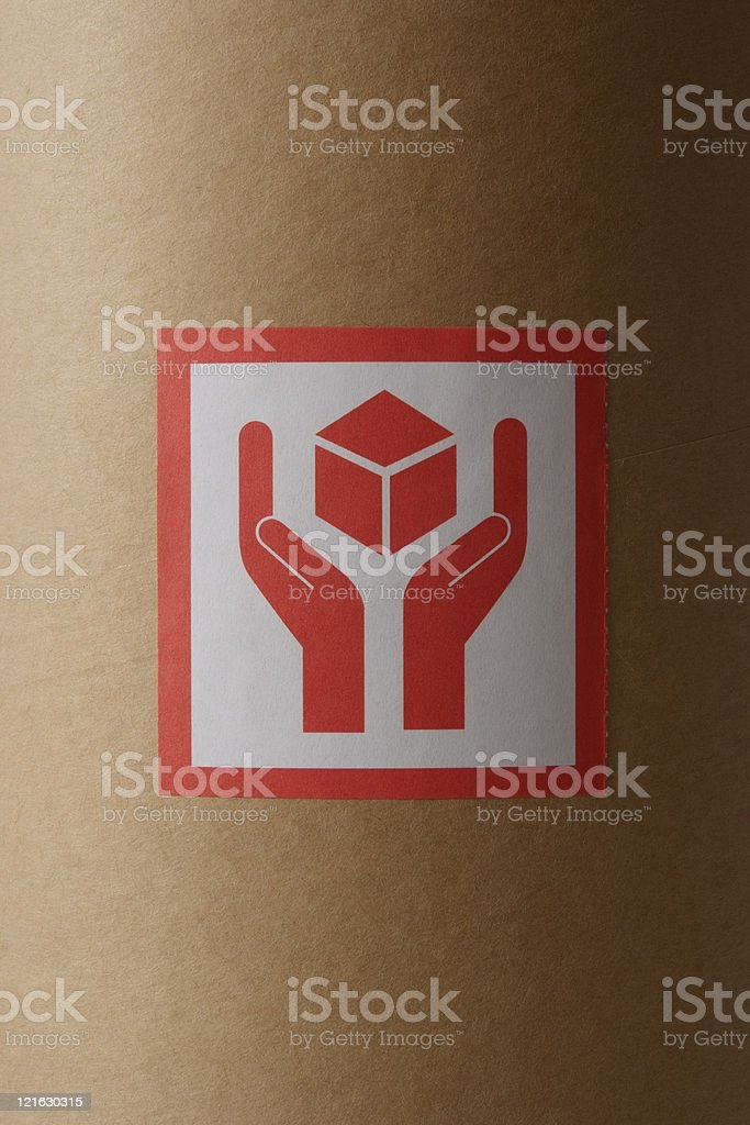 Close-up of red fragile sticker on cardboard cylinder royalty-free stock photo