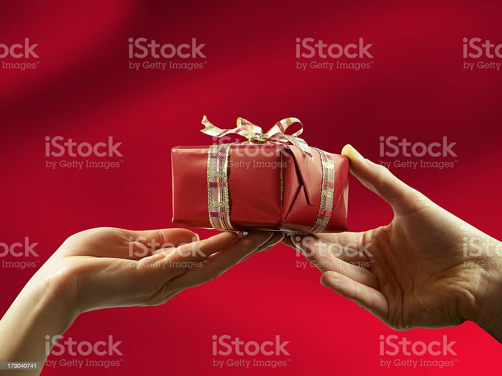 Close-up of red gift box with ribbon, giving from man to woman.
