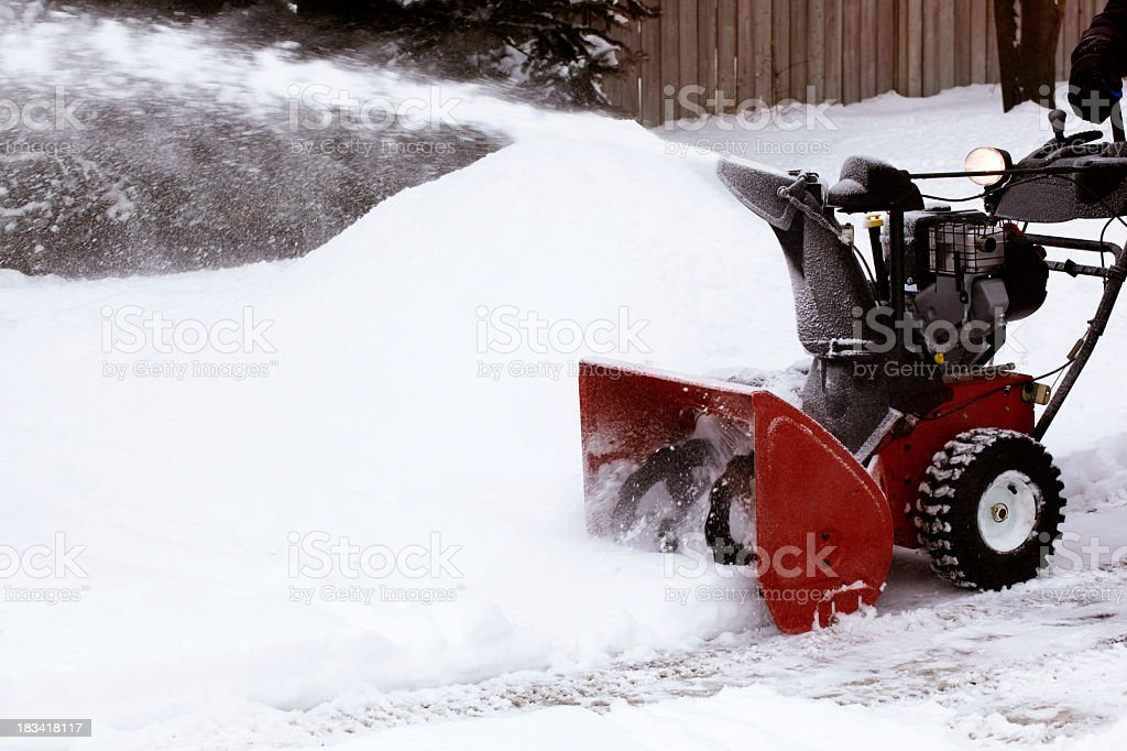 Close-up of red snowblower clearing snow-filled lane stock photo