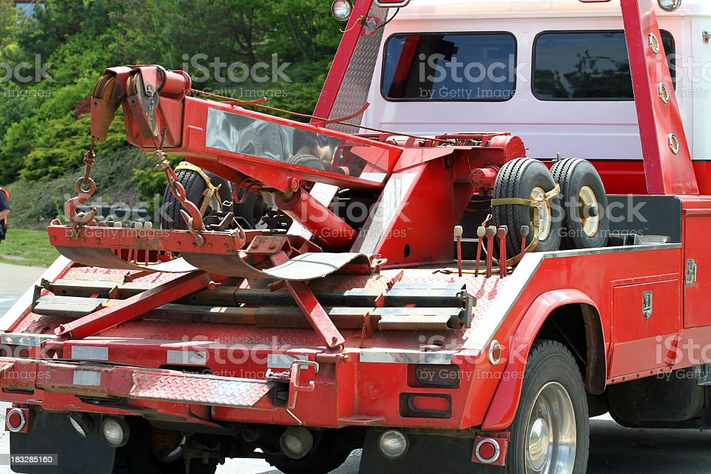 Close-up of red tow truck in a road near trees stock photo