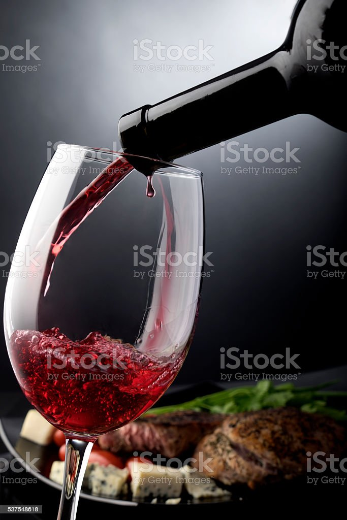 Closeup of red wine pouring into a glass stock photo