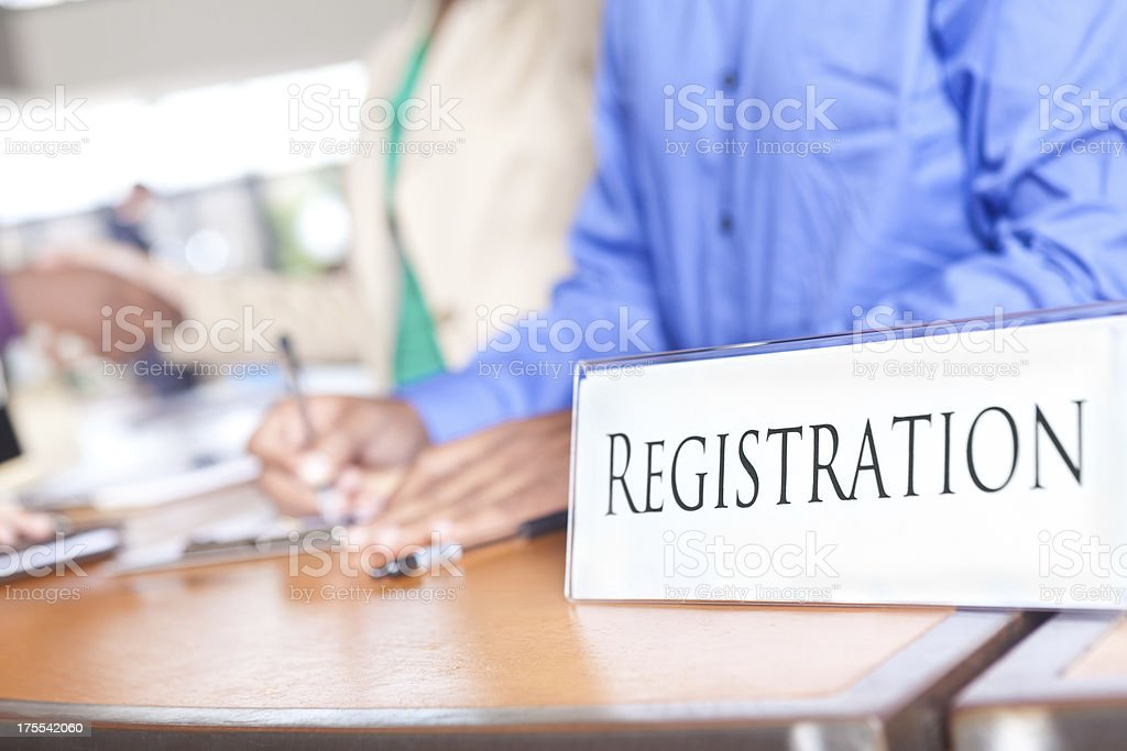 Closeup of Registration desk with people registering at an event stock photo