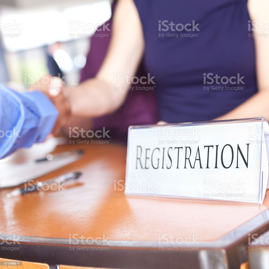 Closeup of Registration desk with people shaking hands stock photo