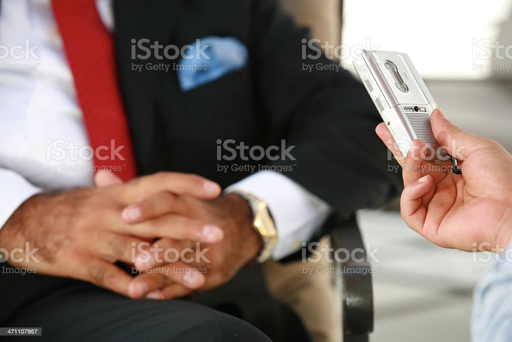 Close-up of reporter's hands, recorder and interview subject stock photo