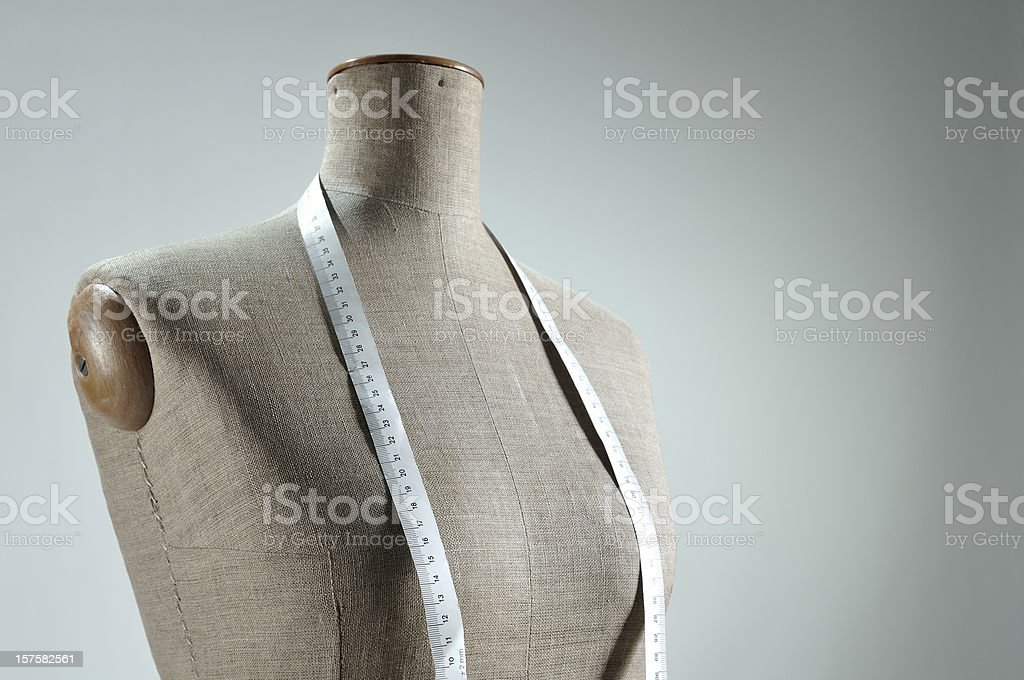 Close-up of retro female tailor's mannequin torso with measuring tape stock photo