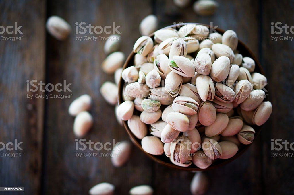 Close-up of roasted pistachios on wooden background stock photo