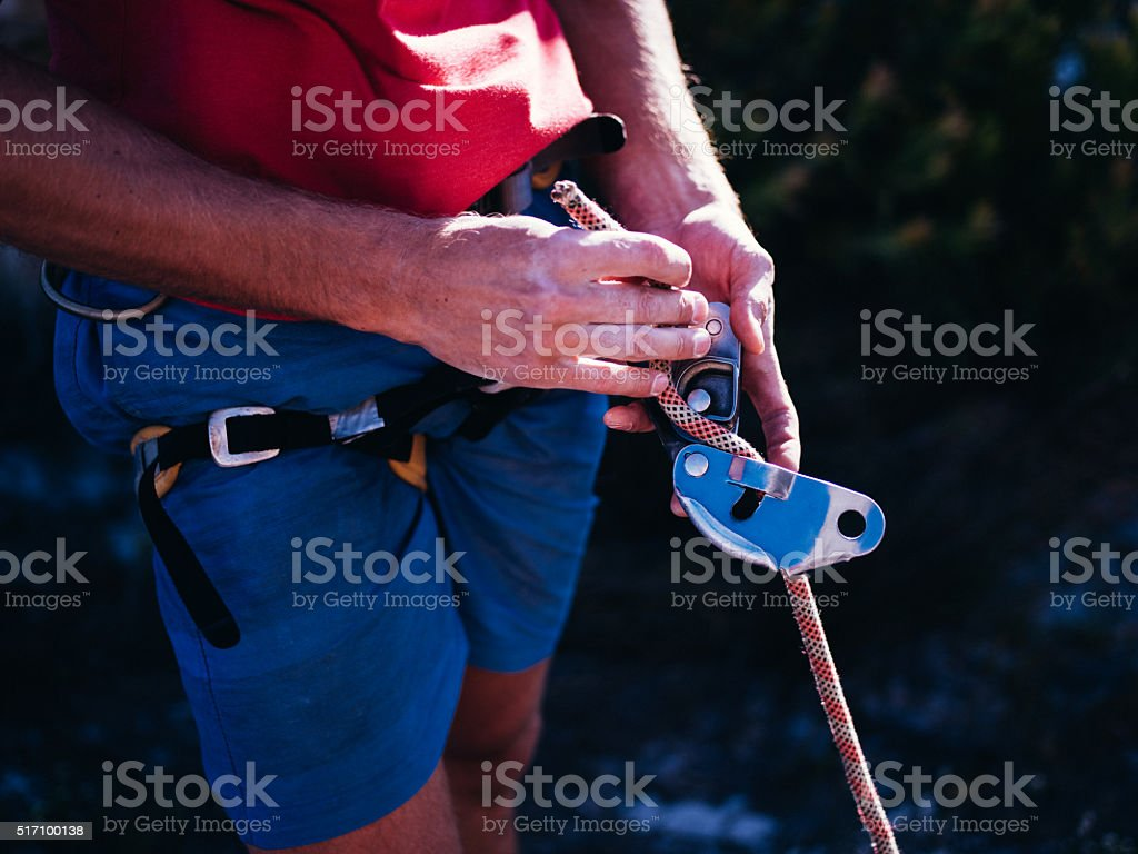 Closeup of rock climber hand's tying knot with belaying rope stock photo