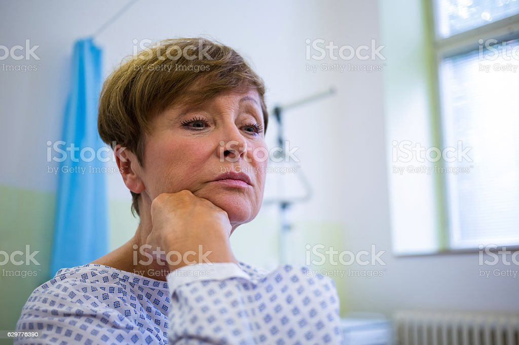 Close-up of sad senior patient sitting on a bed stock photo