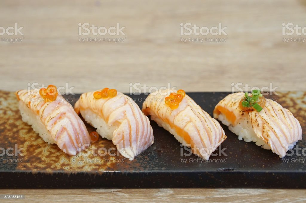 Closeup of salmon sushi on a white plate with salmon roe and chopped spring onion, Aburi style refers to nigiri sushi, the fish is partially grilled topside and partially raw. stock photo
