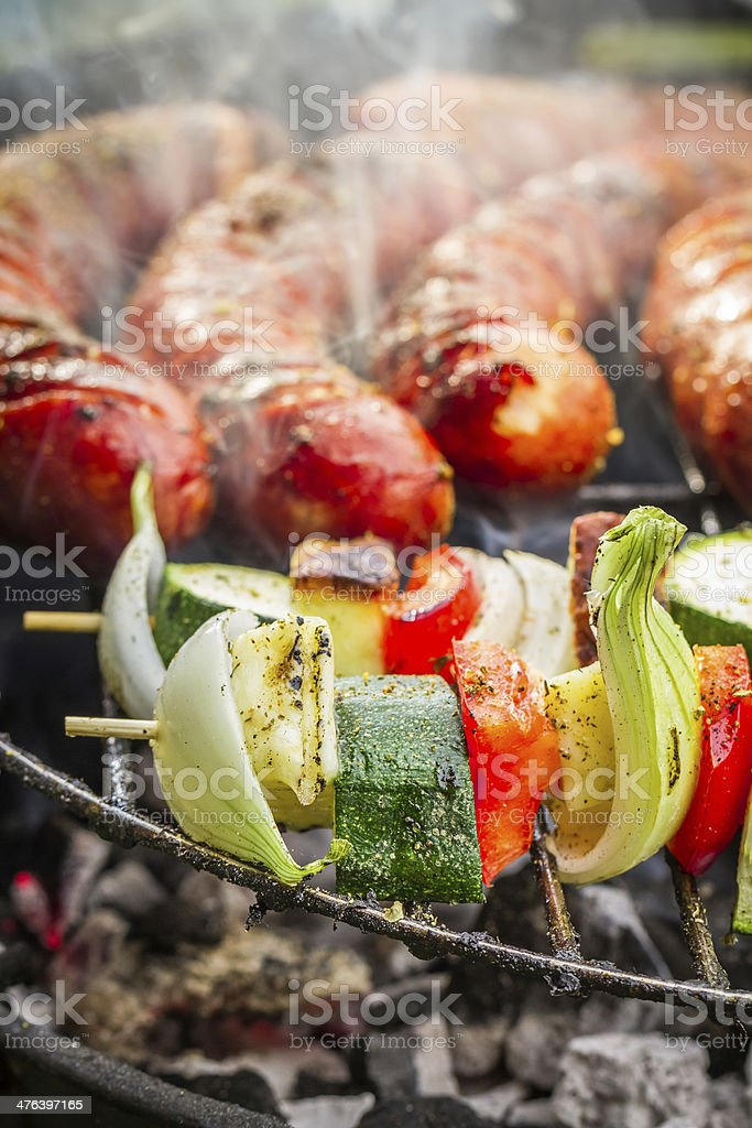 Closeup of sausages and skewers on the grill royalty-free stock photo
